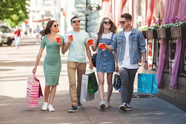 Grupa Młodych Atrakcyjnych Ludzi Dokonywanie Zakupów. Przyjaciele Na Zewnątrz Trzyma Torby Na Zakupy I Uśmiecha Się. Radośni Przyjaciele Razem. Premium Zdjęcia