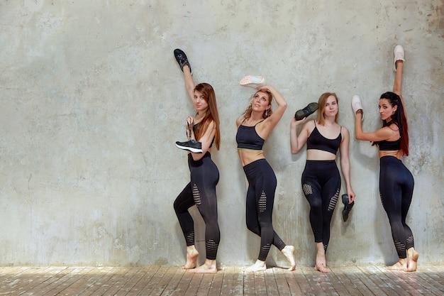 Grupa młodych dziewcząt sportowych odpoczynku po treningu w przestronnym studio na poddaszu. Premium Zdjęcia