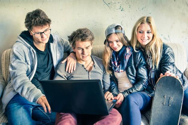 Grupa młodych hipster najlepszych przyjaciół z komputerem w miejskim alternatywnym studiu Premium Zdjęcia