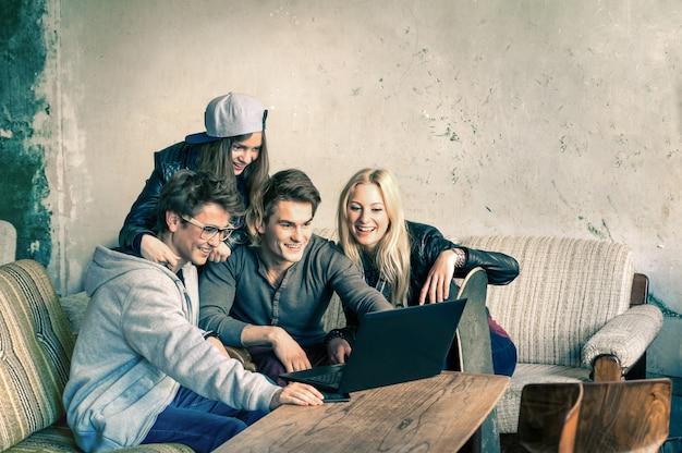 Grupa młodych hipster najlepszych przyjaciół z laptopa komputerowego w miejskiej alternatywnej lokalizacji Premium Zdjęcia