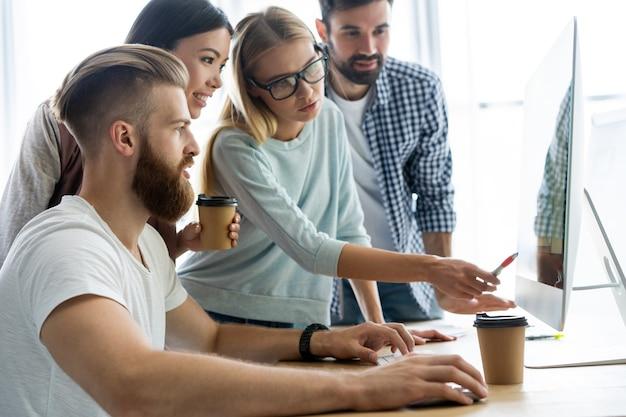 Grupa Młodych Ludzi Biznesu Wesoły, Pracujących I Komunikujących Się Przy Biurku Razem Premium Zdjęcia