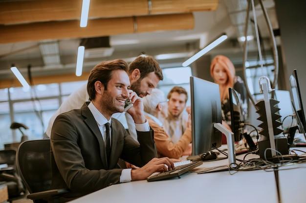 Grupa Młodych Ludzi Biznesu Współpracuje Z Komputerem Stacjonarnym Premium Zdjęcia