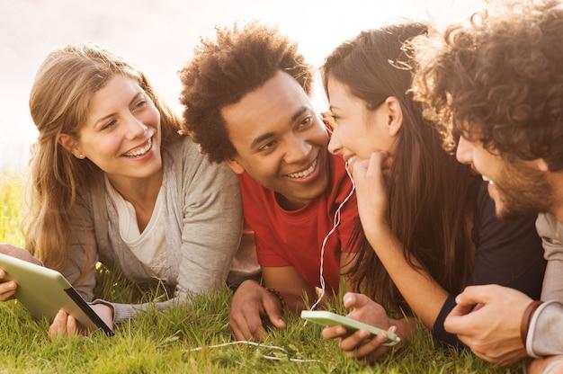 Grupa Młodych Ludzi Wielorasowych Posiadających Cyfrowy Tablet I Telefon Na Zewnątrz Premium Zdjęcia