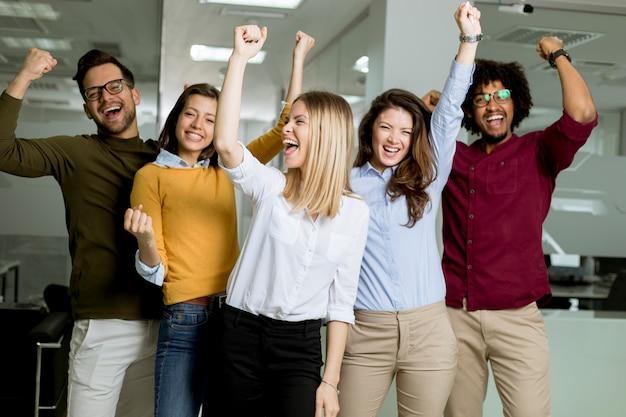 Grupa młodych podekscytowanych ludzi biznesu z rękami w górze stoi w biurze Premium Zdjęcia