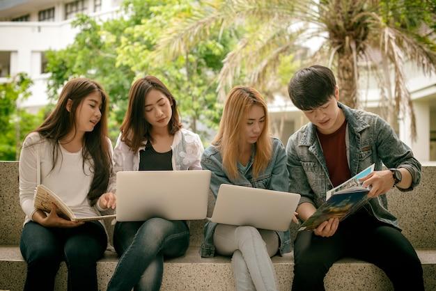 Grupa młodych studentów z raportem grupy roboczej książek i zeszytów siedzi na stole Premium Zdjęcia