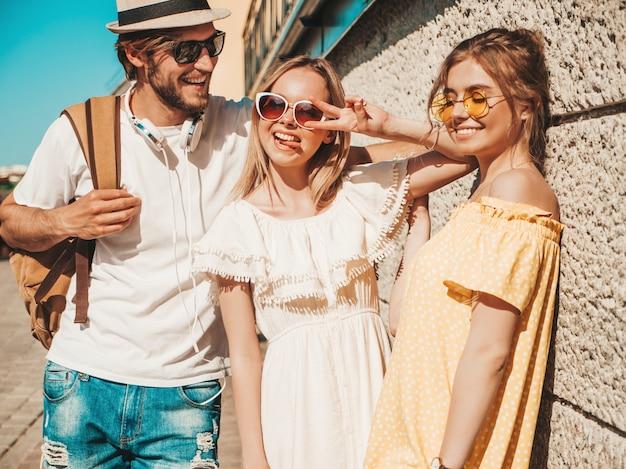 Grupa Młodych Trzech Stylowych Przyjaciół Pozowanie Na Ulicy. Moda Mężczyzna I Dwie Słodkie Dziewczyny Ubrane W Letnie Ubrania. Uśmiechnięte Modele Zabawy W Okularach Przeciwsłonecznych. Piękne Kobiety I Facet Na Zewnątrz Darmowe Zdjęcia