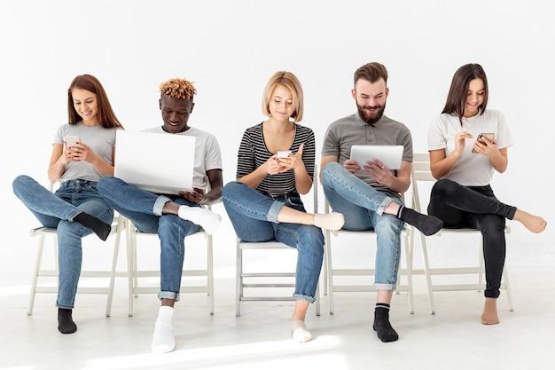 Grupa młodzi przyjaciele siedzi na krzesłach Darmowe Zdjęcia
