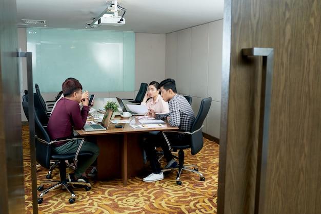 Grupa Niedbale Ubrani Koledzy Siedzi W Biurze Za Otwarte Drzwi I Opowiada Darmowe Zdjęcia