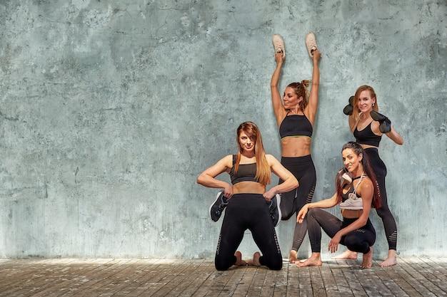 Grupa pięknych dziewczyn fitness pozowanie z akcesoriów sportowych na szarej ścianie Premium Zdjęcia