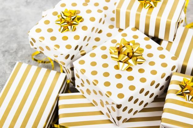 Grupa prezentów w kolorze białym i złotym na szaro Premium Zdjęcia