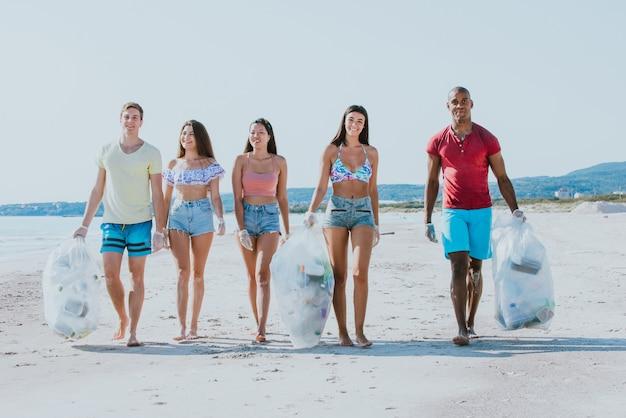 Grupa Przyjaciół Aktywistów Zbierających Odpady Z Tworzyw Sztucznych Na Plaży. Ludzie Sprzątający Plażę Z Workami. Pojęcie Problemów Ochrony środowiska I Zanieczyszczenia Oceanów Premium Zdjęcia
