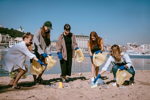 Grupa Przyjaciół Aktywistów Zbierających Odpady Z Tworzyw Sztucznych Na Plaży. Ochrona środowiska. Darmowe Zdjęcia