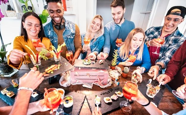 Grupa Przyjaciół Bawi Się Na Przyjęciu W Formie Bufetu, Pijąc Spritz Koktajl I Jedząc Przekąski Premium Zdjęcia