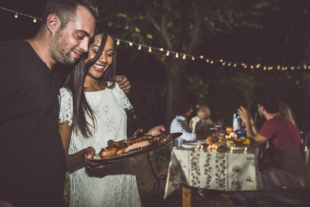 Grupa Przyjaciół Co Grill Na Podwórku W Czasie Kolacji Premium Zdjęcia