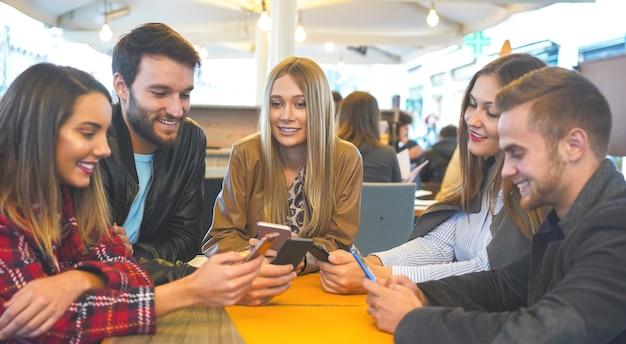 Grupa Przyjaciół Spędzających Czas Ze Sobą Siedząc W Barze Przy Użyciu Telefonów Komórkowych Premium Zdjęcia