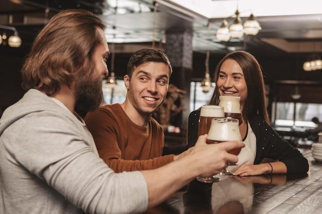 Grupa przyjaciół świętuje w pubie, pijąc piwo razem Premium Zdjęcia