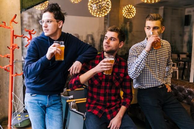 Grupa Przyjaciół, Trzymając Szklanki Piwa Patrząc Od Hotelu Darmowe Zdjęcia