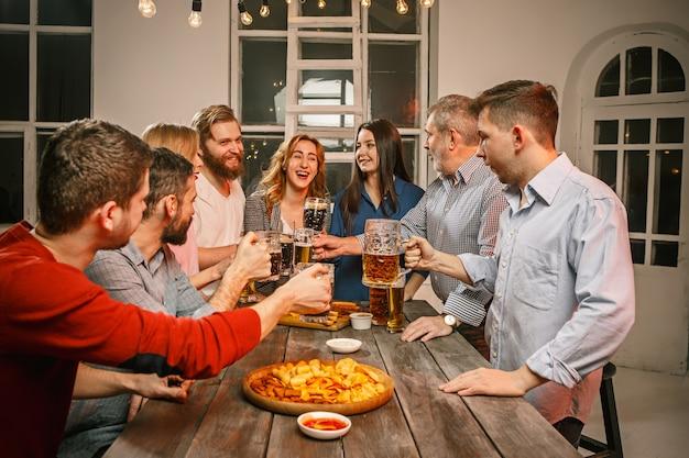 Grupa Przyjaciół Wieczorem Drinki Z Piwem Na Drewnianym Stole Darmowe Zdjęcia