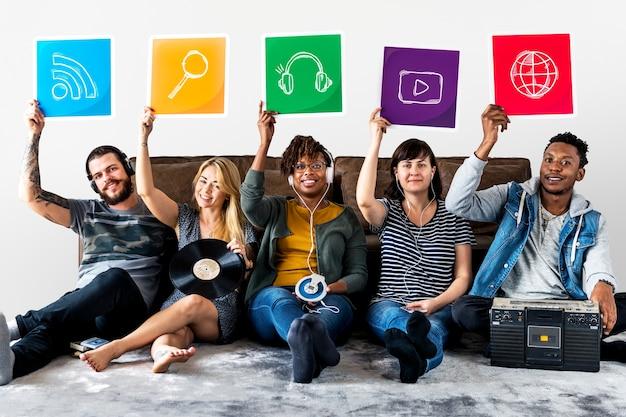 Grupa różnorodni przyjaciele trzyma technologii ikony Premium Zdjęcia