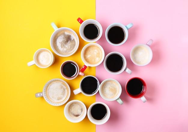 Grupa Różnych Filiżanek Kawy Na Tle żółtym I Różowym. Widok Z Góry, Płaski Układ, Miejsce Na Kopię. Premium Zdjęcia