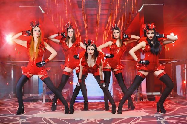Grupa Seksownych Tancerek W Czerwonych Pasujących Strojach Wykonujących Darmowe Zdjęcia