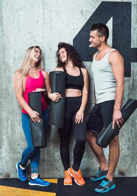 Grupa szczęśliwi dysponowani ludzie opiera na ścianie w gym Darmowe Zdjęcia
