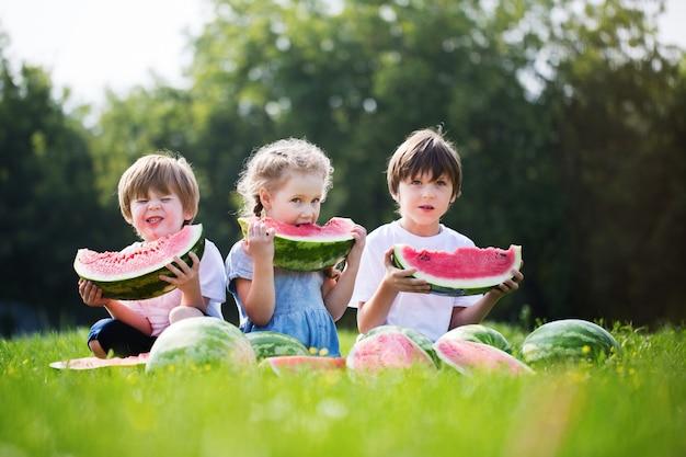 Grupa Szczęśliwi Dzieciaki Je Arbuzy Plenerowych. Premium Zdjęcia