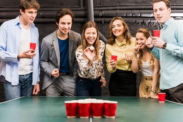 Grupa szczęśliwi uśmiechnięci przyjaciele cieszy się piwną pong grę na stole w barze Darmowe Zdjęcia