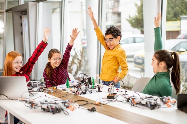 Grupa Szczęśliwych Dzieciaków Programujących Zabawki Elektryczne I Roboty W Klasie Robotyki Premium Zdjęcia