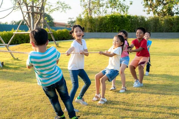 Grupa Szczęśliwych Młodych Azjatyckich Dzieci Bawiące Się Przeciąganie Liny Lub Ciągnięcie Liny Razem Na Zewnątrz W Parku Miejskim Placu Zabaw W Letni Dzień. Koncepcja Dzieci I Rekreacji. Premium Zdjęcia