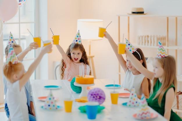 Grupa Wesołych Dzieci W Wieku Przedszkolnym Wspólnie świętować Urodziny, Bawić Się, Kibicować Filiżankom Napojów, Nosi świąteczne Kapelusze, Jeść Pyszne Ciasto Premium Zdjęcia