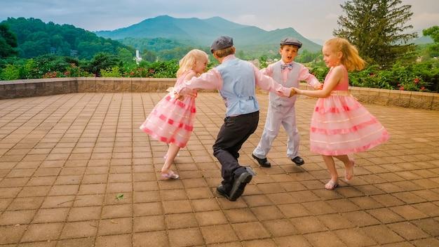 Grupa Wesołych Dzieciaków Bawiących Się I Tańczących Razem Na Terenie Otoczonym Piękną Zielenią Darmowe Zdjęcia
