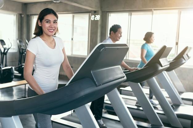 Grupowy azjatykci rodzinny ćwiczenie biegacz przy gym sprawnością fizyczną uśmiechniętą i szczęśliwą. zdrowy tryb życia. Premium Zdjęcia