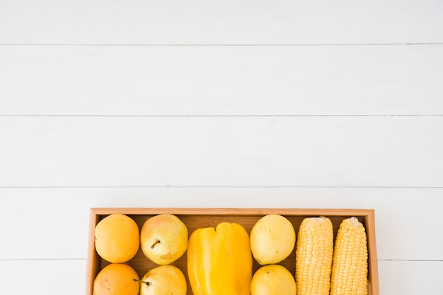 Gruszki; Papryka I Kukurydza Na Drewnianej Tacy Nad Białym Stołem Darmowe Zdjęcia
