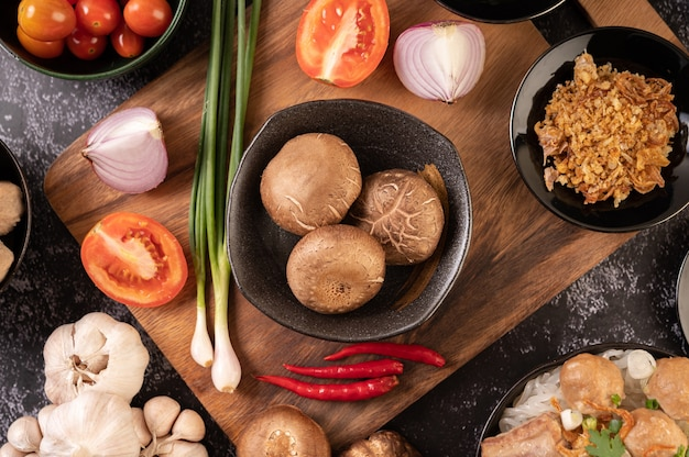 Grzyby Shiitake Z Czosnkiem, Pomidorem, Papryką, Szczypiorkiem I Czerwoną Cebulą Na Podłodze Z Czarnego Cementu. Darmowe Zdjęcia