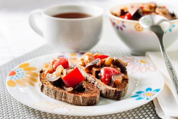 Gulasz Warzywny Z Bakłażanem, Czerwoną Papryką I Pomidorami Na Prażonym Chlebie żytnim Premium Zdjęcia