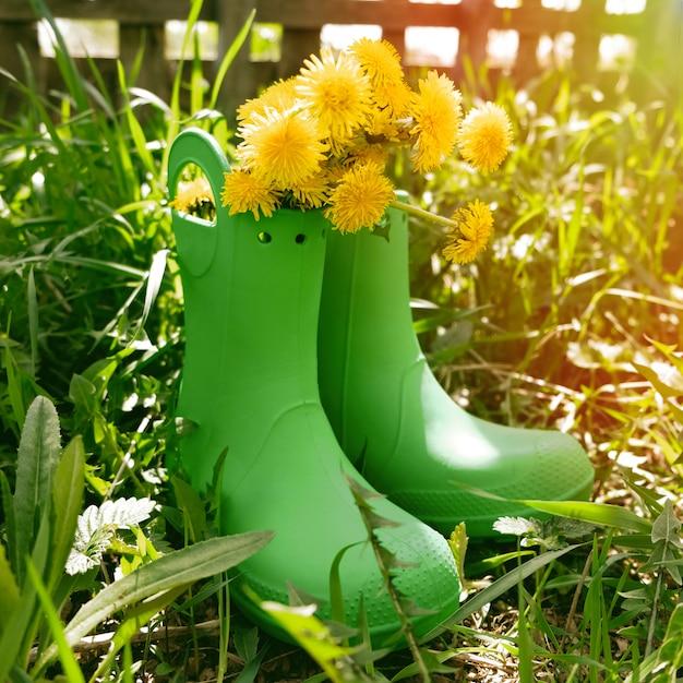 Gumowe Buty Z Kwiatami W Zielonej łące Premium Zdjęcia