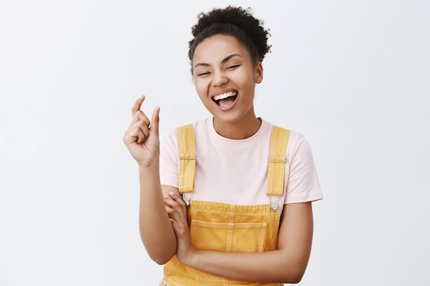 Ha Ha Taki Mały. Portret Radosnej, Wzruszającej Młodej Kobiety O Ciemnej Skórze I Kręconych Włosach, Kształtującej Mały I Zabawny Przedmiot Palcami, Głośno Się śmiejącej, Besztającej Kogoś Z Powodu Rozmiaru Na Szarej ścianie Darmowe Zdjęcia