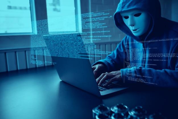 Hakerzy azjatyccy noszą maskę za pomocą cyberataku na laptopie. Premium Zdjęcia