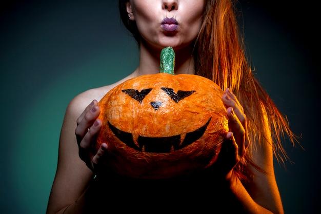 Halloween, kobieta w bieliźnie z dynią w ręku. Premium Zdjęcia