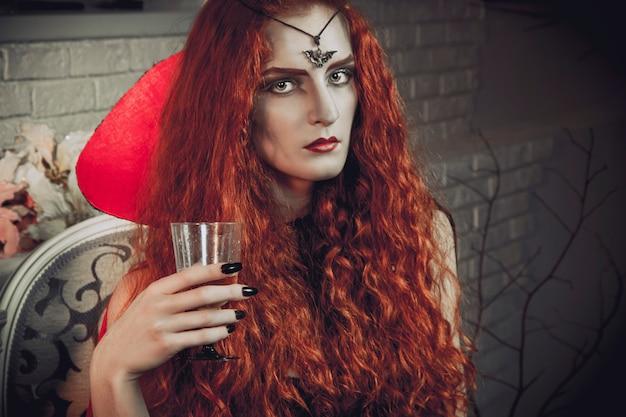 Halloweenowa wiedźma przygotowuje się do święta zmarłych. rudowłosa czarodziejka Premium Zdjęcia