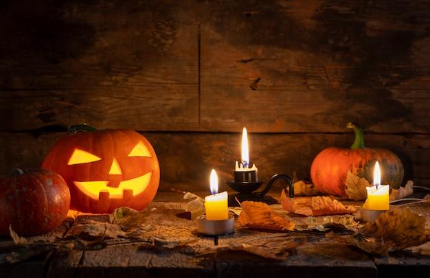 Halloweenowe banie przewodzą jack o lampion na drewnianym stole w tajemniczym lesie przy nocą. Premium Zdjęcia