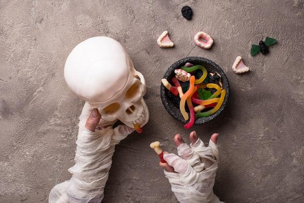 Halloweenowe Tło Z Rękami, Słodyczami I Czaszką Mumii Premium Zdjęcia