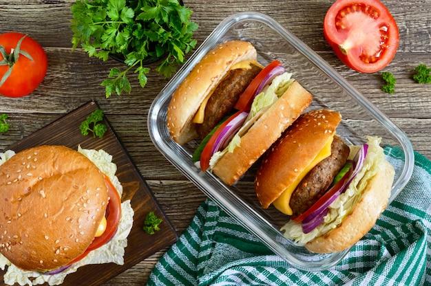 Hamburgery Z Soczystym Kotletem, świeżymi Warzywami, Chrupiącą Bułeczką Z Sezamem Na Drewnianym Stole. Tradycyjne Fast Foody. Widok Z Góry, Leżał Płasko Premium Zdjęcia