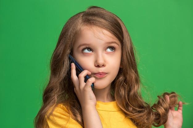 Happy Teen Dziewczyny Stojącej, Uśmiechając Się Z Telefonu Komórkowego Na Modnej Zieleni. Piękny Portret Kobiety W Połowie Długości Darmowe Zdjęcia