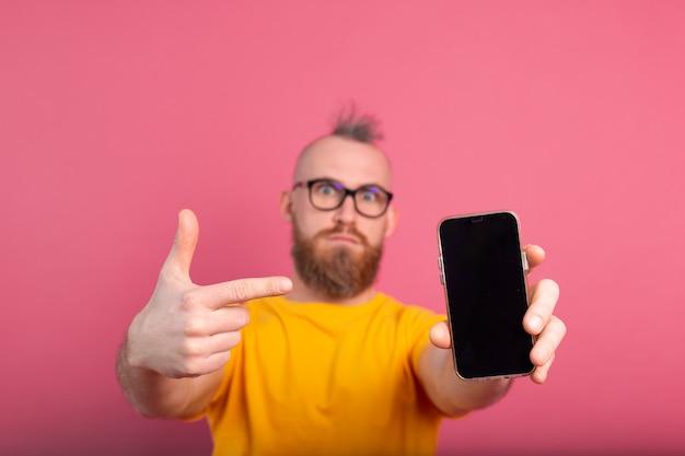 Hej, Coś Nowego. Poważny Zły Europejski Brodaty Facet Wskazujący Na Swój Telefon Komórkowy Z Czarnym Pustym Ekranem Na Różowo Darmowe Zdjęcia