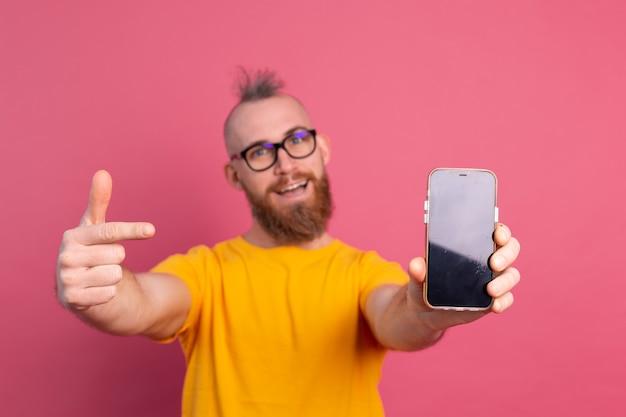 Hej, Coś Nowego. Szczęśliwy Europejski Brodaty Facet Wskazując Swój Telefon Komórkowy Z Czarnym Pustym Ekranem Na Różowo Darmowe Zdjęcia