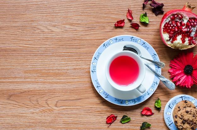 Herbata owocowa z cytryną, mlekiem, miodem, pomarańczą, granatem, na drewnianym tle Premium Zdjęcia