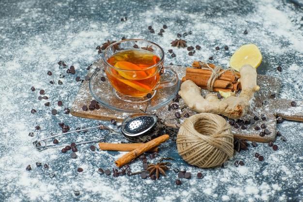 Herbata W Kubku Z Mąką, Chipsami Czekoladowymi, Sitkiem, Przyprawami, Cytryną Pod Dużym Kątem Na Betonie I Desce Do Krojenia Darmowe Zdjęcia