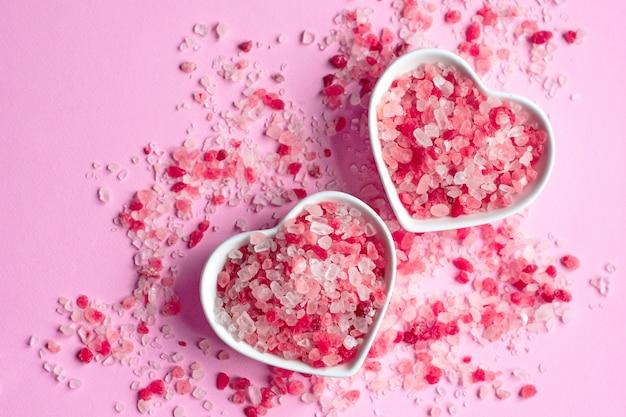 Himalajska Różowa Sól Na Różowym Papierowym Stole W Spodku W Kształcie Serca Premium Zdjęcia